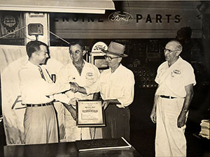 James W. Sneed, in hat, in front of the parts department at Sunrise Ford at its first formal location