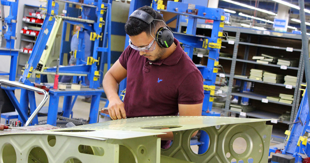 A worker assembles a part that will become a wing of a Piper Aircraft plane made in Vero Beach