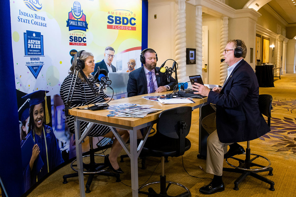 Tom Kindred, right, regional director for Florida SBDC at IRSC, interviews Melissa Roberts, managing director of operations, Jim Moran Institute, and Michael Myhre